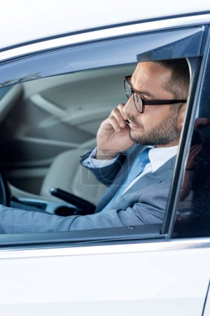 side view of businessman in eyeglasses talking on smartphone while driving car