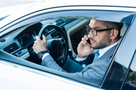 Photo for Side view of businessman in eyeglasses talking on smartphone while driving car - Royalty Free Image