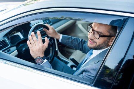 Lächelnder Geschäftsmann in Anzug und Brille grüßt beim Autofahren