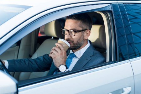 Photo for Side view of businessman in eyeglasses with coffee to go driving car - Royalty Free Image