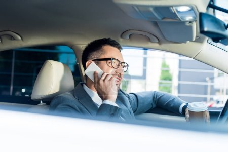 side view of smiling businessman with coffee to go talking on smartphone in car