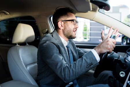side view of emotional businessman in suit and eyeglasses driving car alone