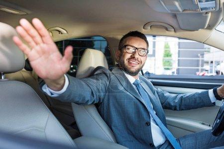 Photo pour Homme d'affaires souriant en costume et lunettes saluant quelqu'un tout en conduisant une voiture - image libre de droit