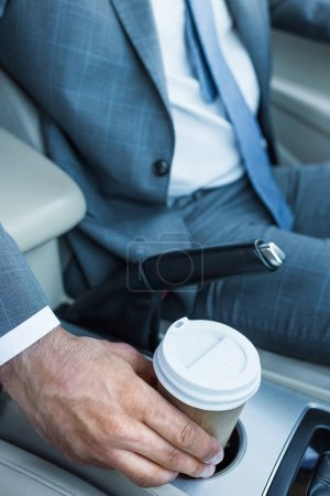 cropped shot of businessman taking coffee to go in car