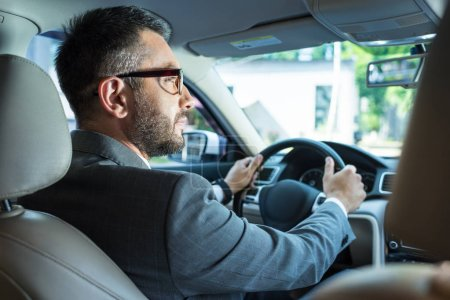 Photo for Back view of businessman in suit and eyeglasses driving car alone - Royalty Free Image