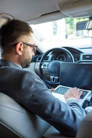 side view of businessman in eyeglasses using laptop with blank screen in car