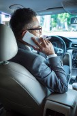 back view of businessman talking on smartphone while driving car