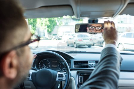 Photo for Partial view of businessman in eyeglasses looking at rear view mirror in car - Royalty Free Image