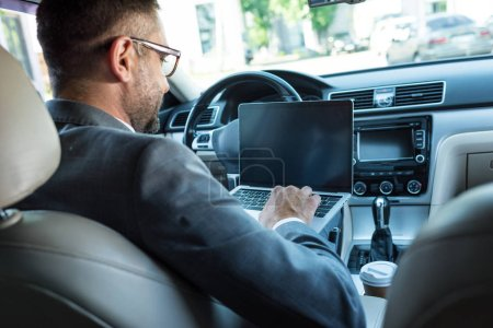 back view of businessman in eyeglasses using laptop with blank screen in car