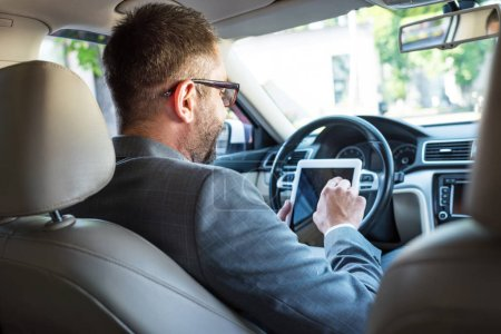 partial view of businessman in eyeglasses using tablet in car