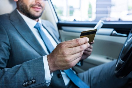 partial view of businessman with tablet and credit card sitting in car