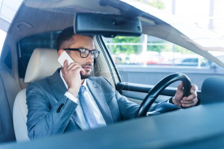 side view of businessman talking on smartphone while driving car