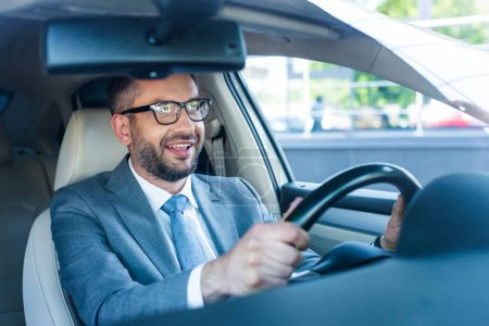 portrait of smiling businessman in suit and eyeglasses driving car alone