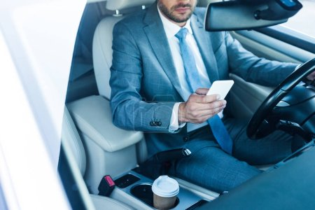 partial view of businessman using smartphone in car