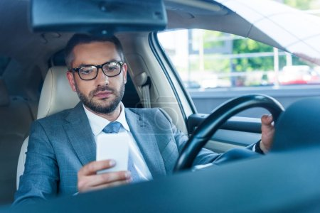 portrait of businessman in eyeglasses using smartphone in car