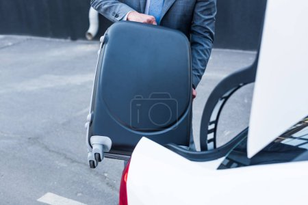cropped shot of businessman putting luggage into car on parking