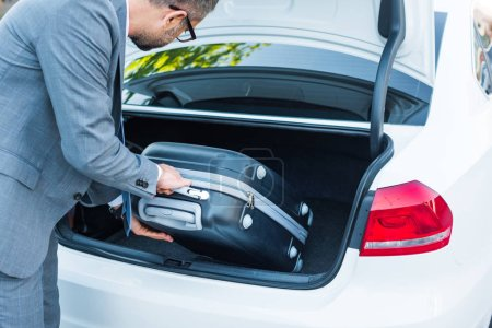 Photo for Partial view of businessman putting luggage into car on parking - Royalty Free Image