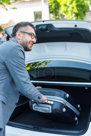 side view of smiling businessman putting luggage into car on parking