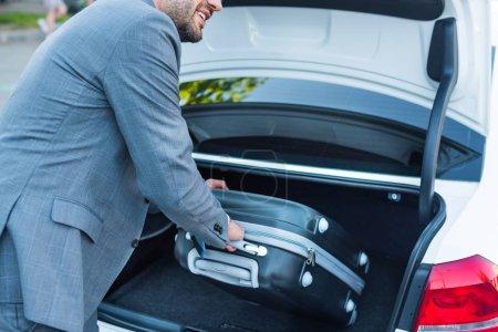 Photo pour Plan recadré de l'homme d'affaires mettre des bagages dans la voiture sur le parking - image libre de droit