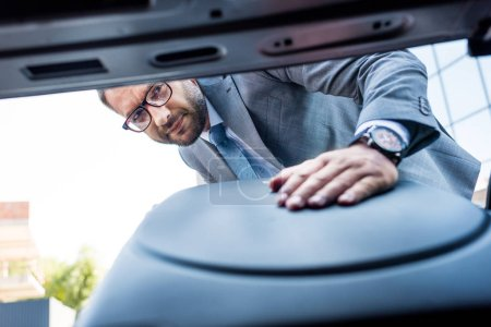 selective focus of businessman in eyeglasses putting luggage into car on parking