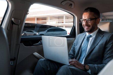 smiling businessman in eyeglasses using laptop on backseat in car