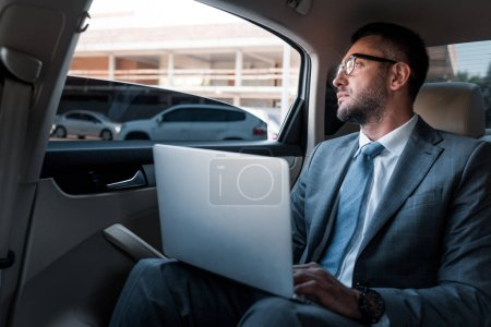 pensive businessman in eyeglasses with laptop looking away on backseat in car