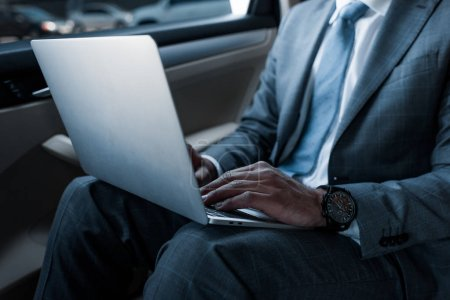 cropped shot of businessman in using laptop on backseat in car