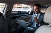smiling businessman in eyeglasses with coffee to go using laptop on backseat in car