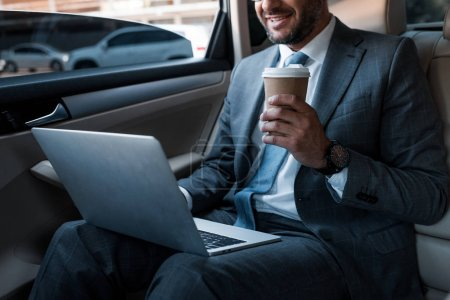 cropped shot of smiling businessman with coffee to go using laptop on backseat in car