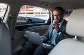 businessman in eyeglasses with coffee to go using laptop in car
