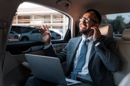 businessman in earphones with laptop listening music in car
