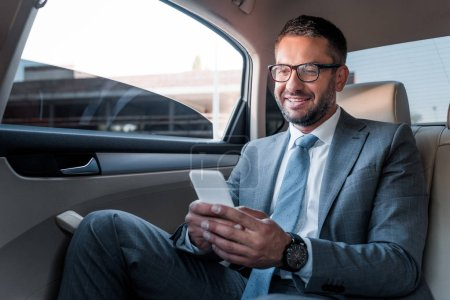 smiling businessman using smartphone on backseat in car