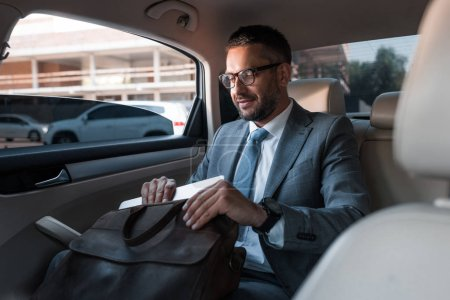 businessman in suit putting papers into bag while sitting on backseat in car