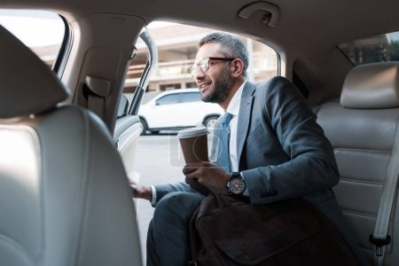 businessman with coffee to go sitting in car with opened door