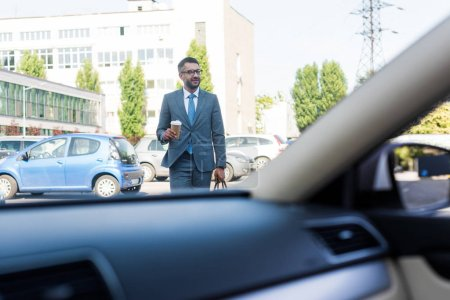 businessman in suit and eyeglasses with coffee to go going to car on street