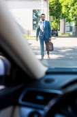 businessman in suit and eyeglasses going to car on street