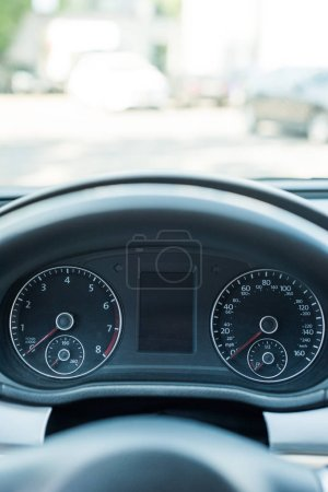 close up view of black speedometer and steering wheel in car