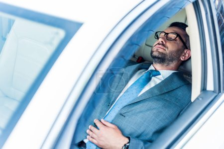 Photo for Tired businessman in eyeglasses sleeping in car - Royalty Free Image