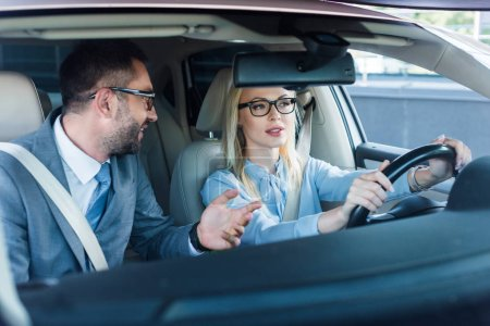 portrait of blonde businesswoman in eyeglasses driving car with colleague near by