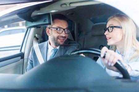 Porträt der blonden Geschäftsfrau mit Brille, die mit einem Kollegen in der Nähe Auto fährt