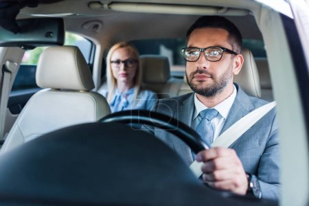 selective focus of businessman in eyeglasses driving car with colleague sitting behind on passengers seat