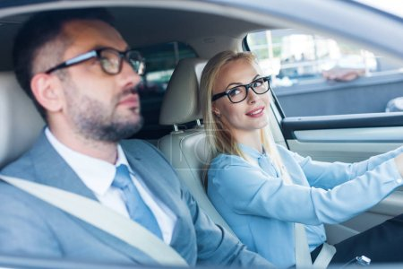 side view of blonde businesswoman in eyeglasses driving car with colleague near by