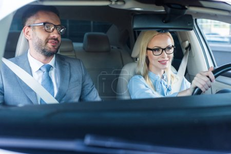 Photo for Portrait of blonde businesswoman in eyeglasses driving car with colleague near by - Royalty Free Image