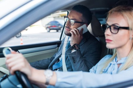 selective focus of businesswoman driving car while colleague talking on smartphone near by on passengers seat
