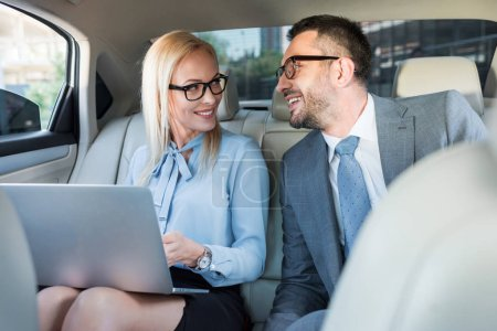 portrait of smiling business people with laptop on back seats in car