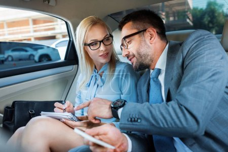 portrait of business people with notebook and smartphone discussing work on back seats in car