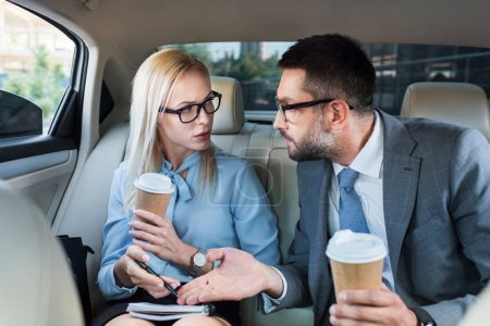 portrait of business people with coffee to go discussing work on back seats in car