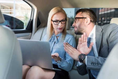 portrait of business people with laptop discussing work on back seats in car