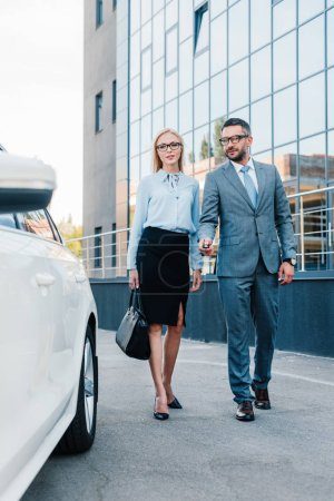 business people in eyeglasses walking to car on parking