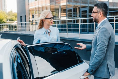 side view of business colleagues having conversation near car on street